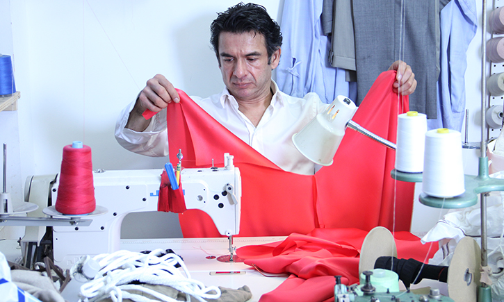 Molina at work in his studio, copying a coat that had been featured in a fashion magazine.