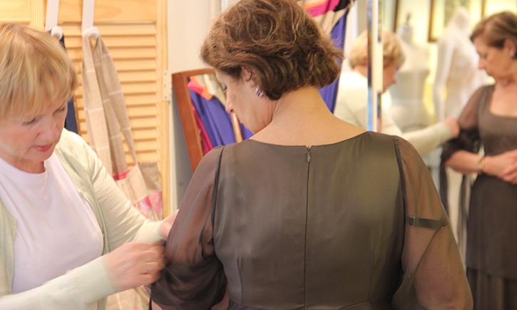 Irene Tcherniakovski adjusts the diaphanous sleeve of a client's evening gown.