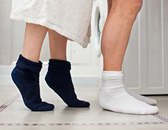 Mature couple in standing in bathroom. Low angle view of couple wearing socks at the bathroom sink.