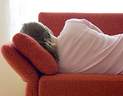 Woman resting on a red couch in the living room.